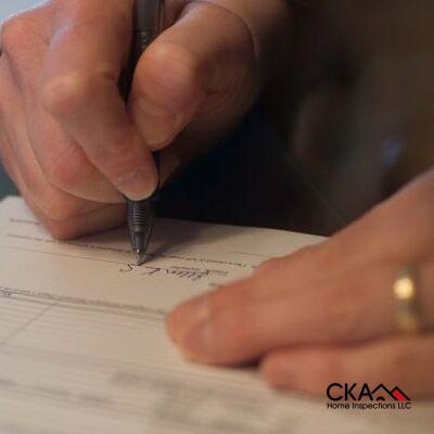 A Man Signing Closing Papers on a Home.